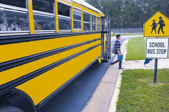 Girl leaving school bus at bus stop